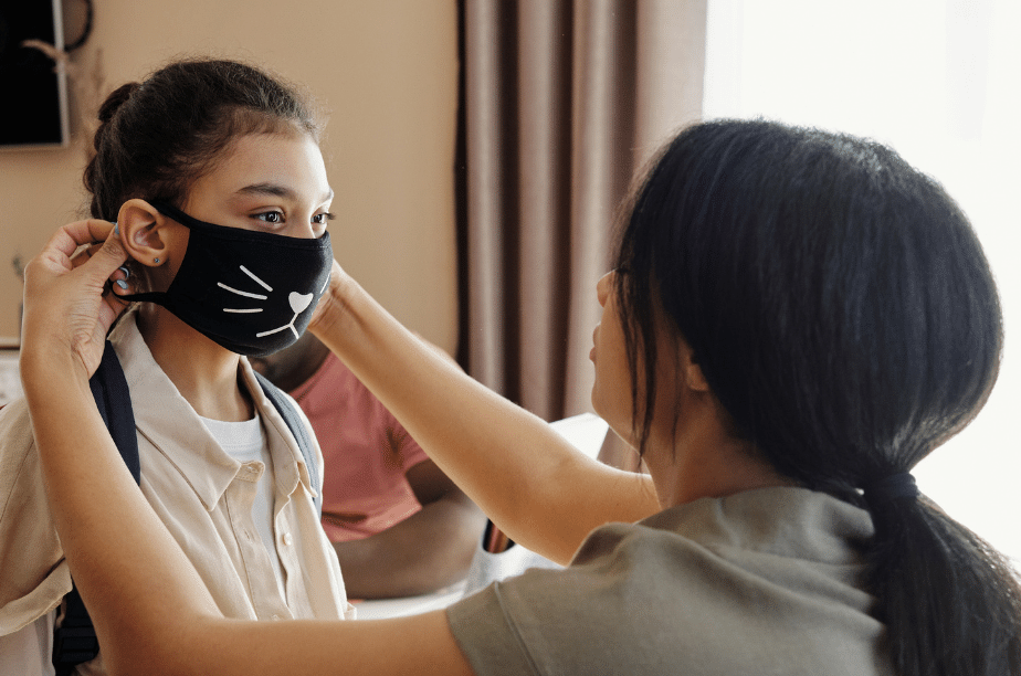 mom helping her daughter put on her mask for school to prevent the spread of covid19 924px x 612px